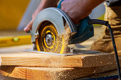 Carpenter using circular saw for cutting wooden boards with hand power tools.