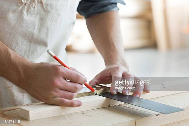Carpenter using mitre in workshop