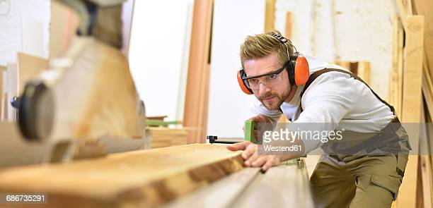 Carpenter using sawing machine in his workshop