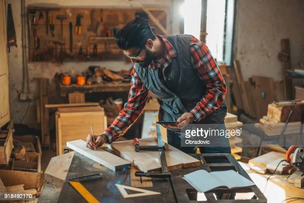 Tischler mit Tablette während der Arbeit in seiner Werkstatt auf Möbel-Projekt