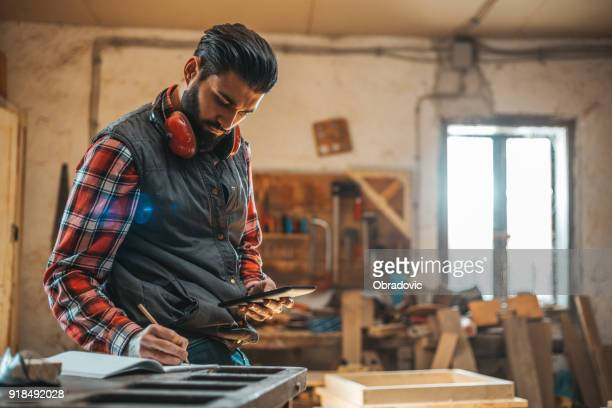 carpenter using tablet while working in his workshop pn furniture project - small business stock photos and pictures