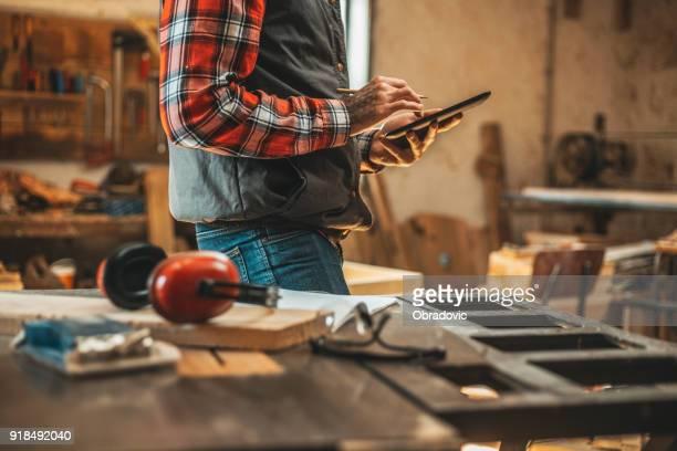 Tischler mit Tablette während der Arbeit in seiner Werkstatt-Pn-Möbel-Projekt