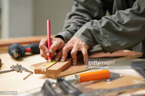 carpenter using tape measure to measure distance and marking with pencil - carpenter stock pictures, royalty-free photos & images