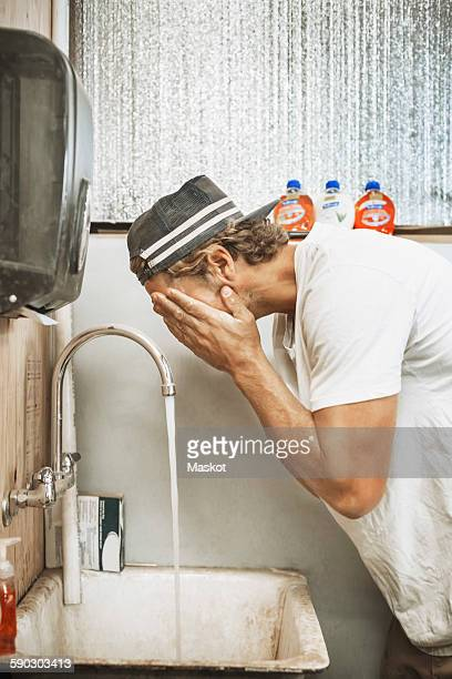 carpenter washing face in workshop - one man only stock pictures, royalty-free photos & images