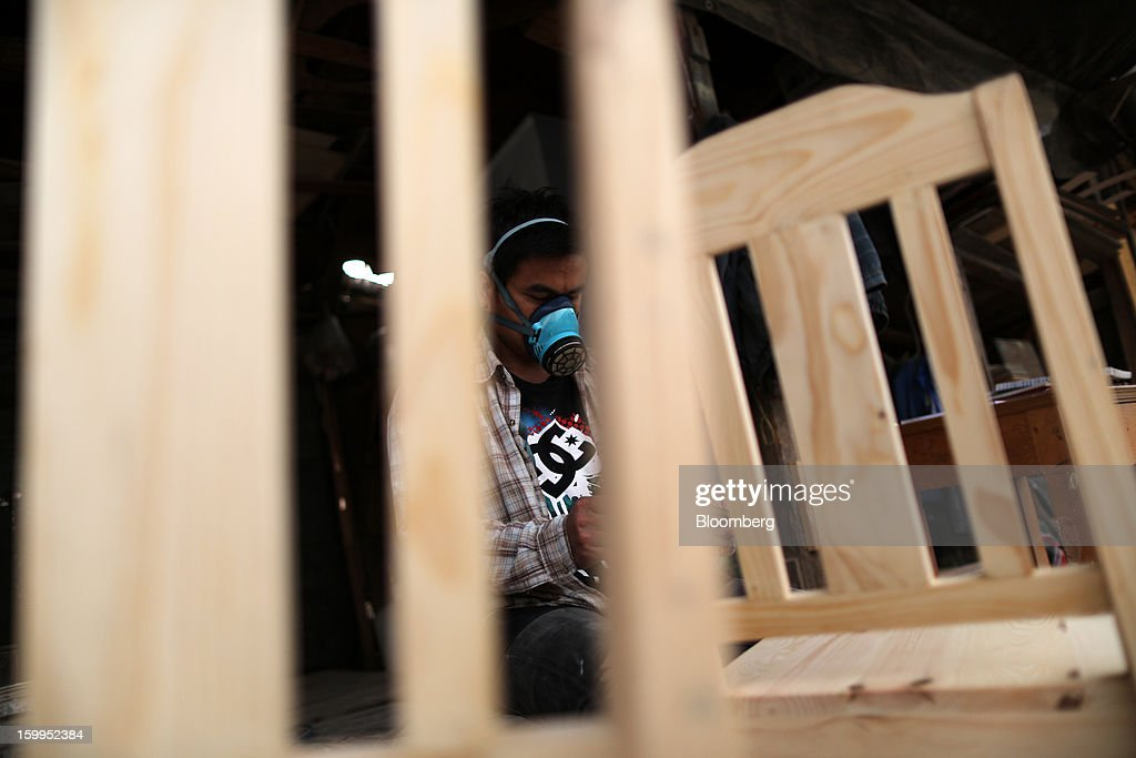 A carpenter wearing a face mask finishes chairs at a workshop in Bangkok, Thailand, on Wednesday, Jan. 23, 2013. Prime Minister Yingluck Shinawatra's government last month approved a new round of increases in the daily minimum wage to 300 baht ($9.8) from the beginning of this year, after a similar raise in April in seven provinces including Bangkok. Photographer: Dario Pignatelli/Bloomberg via Getty Images
