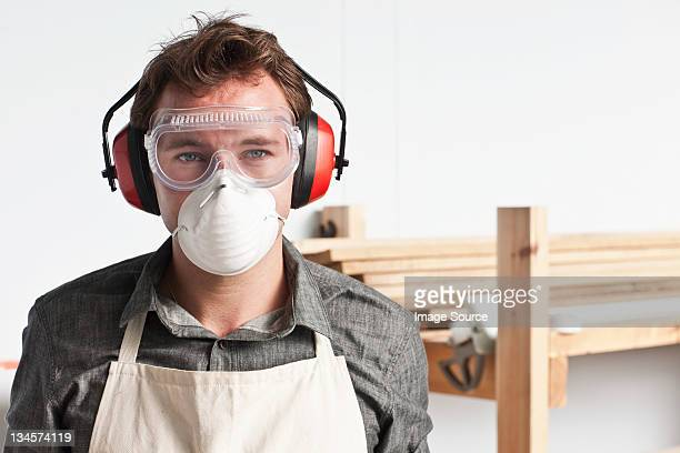 Carpenter wearing dust mask and ear defenders, portrait