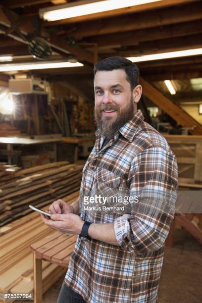 carpenter with cellphone at his workshop