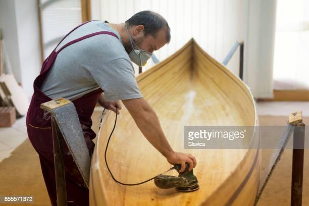 tischler mit gesichtsmaske schmirgeln hölzernes kanu - bauen stock-fotos und bilder