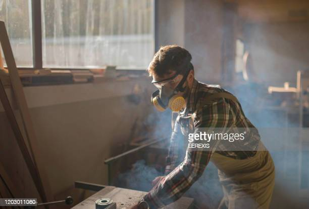 carpenter with mask and glasses in smoke - lerexis stock pictures, royalty-free photos & images