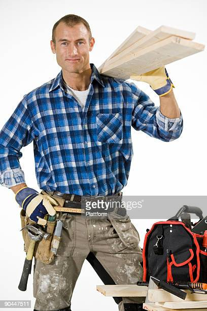 A carpenter with plank and tolls.