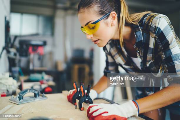 carpenter woman at work using electric saw to cut timber - diy stock pictures, royalty-free photos & images