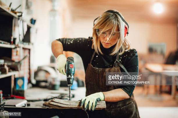 a carpenter woman changing an orbital sander's paper while working in a shop - drill stock pictures, royalty-free photos & images