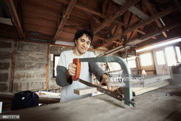 Carpenter woman working with hand saw