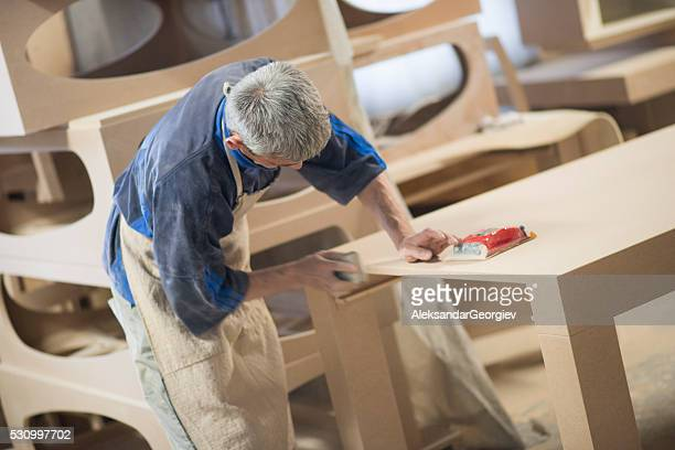 Carpenter Worker Sanding Wooden Table with Sander