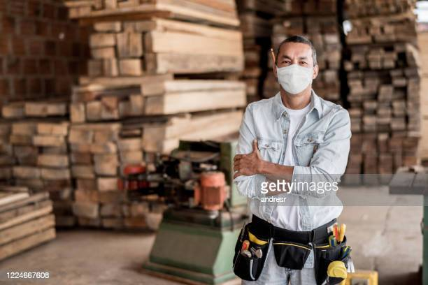 carpenter working at his workshop wearing a facemask to avoid coronavirus - construction worker stock pictures, royalty-free photos & images
