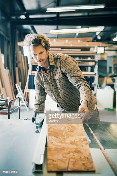 Carpenter working at table in workshop