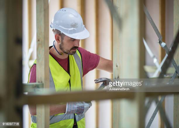 carpenter working on building site - builder stock photos and pictures