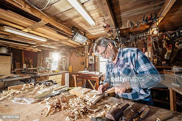 Carpenter working on wood with chisel