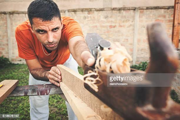 Carpenter working on wooden board