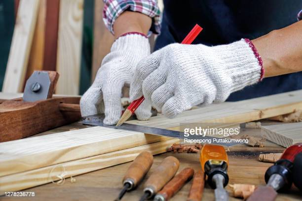 carpenter working on woodworking holding a ruler on the work bench - ものさし ストックフォトと画像