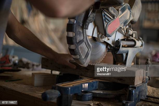 carpenter working with circular saw in workshop - circular saw stock photos and pictures