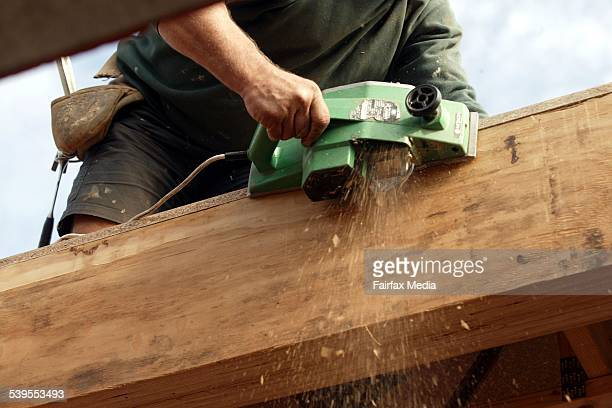 A carpenter works with an electric tool to shave off a timber edge 26 May 2004 AFR Picture by ERIN JONASSON