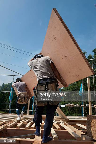Carpenters carry wooden materials at a new home construction site in Yokohama Japan on Monday July 23 2012 Japan's new housing starts last year rose...
