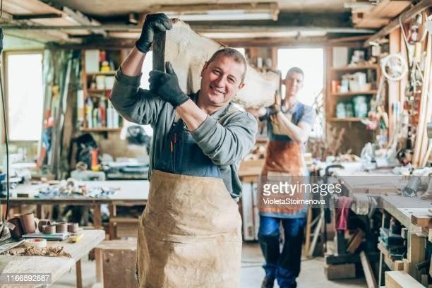 timmerlieden met een houten plank - alleen volwassenen stockfoto's en -beelden