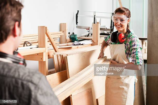 Carpenters carrying wood in workshop