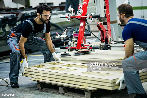 carpenters carrying wood plank - protective workwear stock pictures, royalty-free photos & images