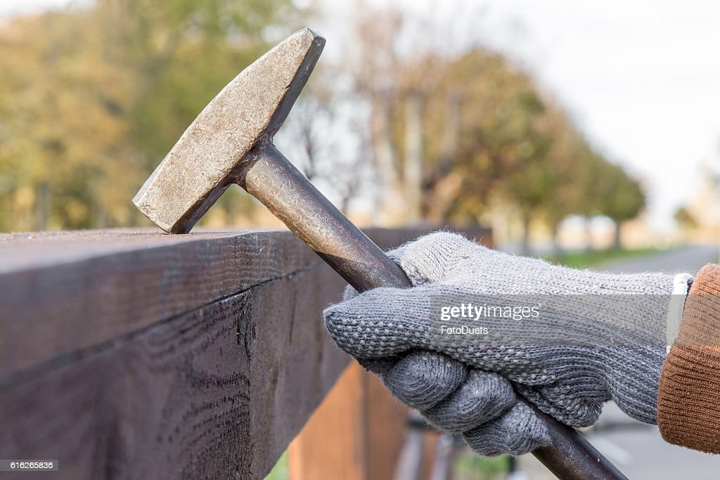 Carpenter's hands beating nails with an old iron hammer. : Stock Photo