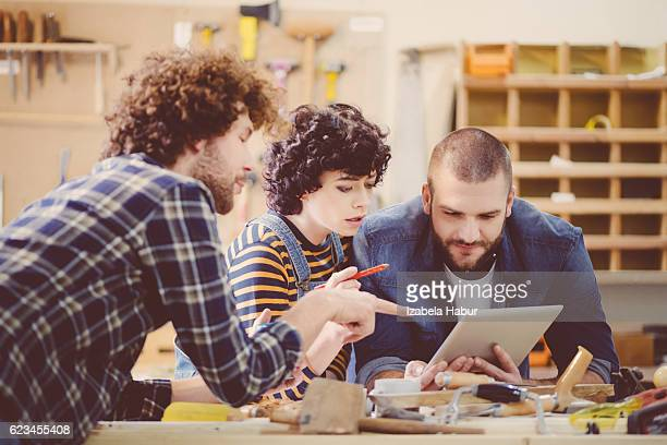 Carpenters in a construction workshop, discussing over digital tablet