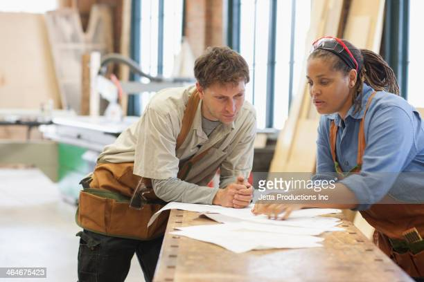Carpenters looking at plans in workshop