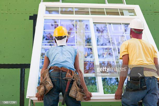 carpenters positioning a large window frame at a construction site - installieren stock-fotos und bilder