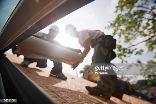 Carpenters preparing underlayment for new roof
