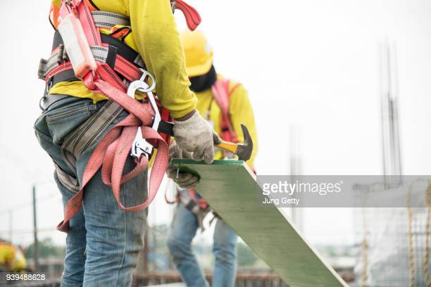 carpenter's tool belt with hammers at construction site - fabricage apparatuur stock pictures, royalty-free photos & images