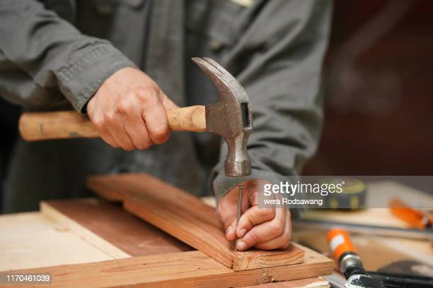carpenters uses a hammer to driving nail - hammer stock pictures, royalty-free photos & images