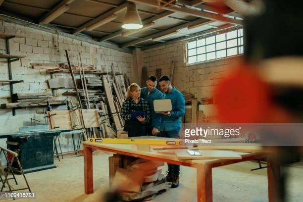 timmerlieden die laptop gebruiken in de werkplaats - mensen op de achtergrond stockfoto's en -beelden