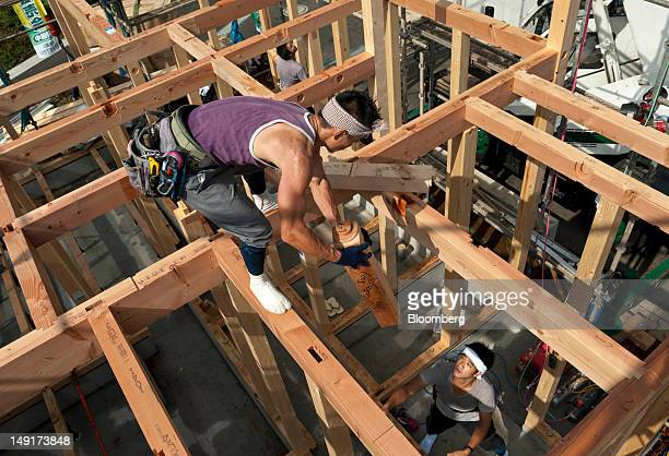 Carpenters work at a new home construction site in Yokohama Japan on Monday July 23 2012 Japan's new housing starts last year rose 26 percent to...