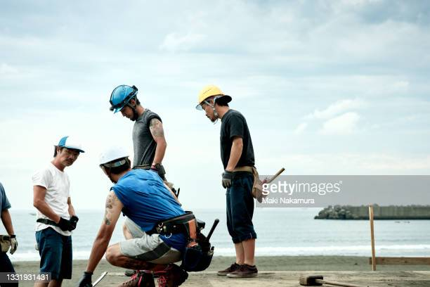 carpenters working with colleagues at a construction site. - chigasaki stock pictures, royalty-free photos & images