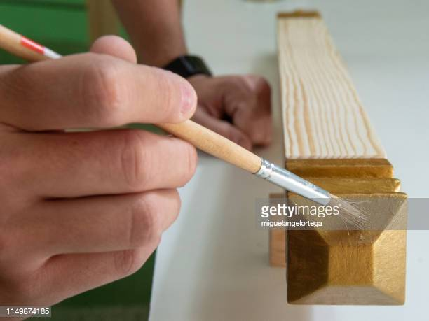carpentry shop - painting a wooden piece - pintura stock photos and pictures
