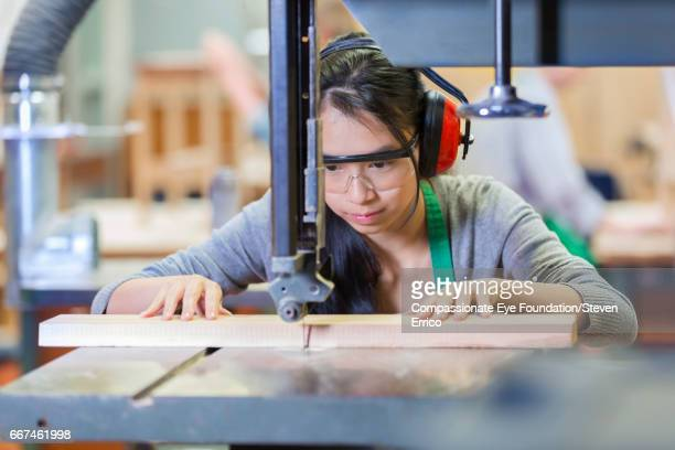 Carpentry student using machinery in workshop