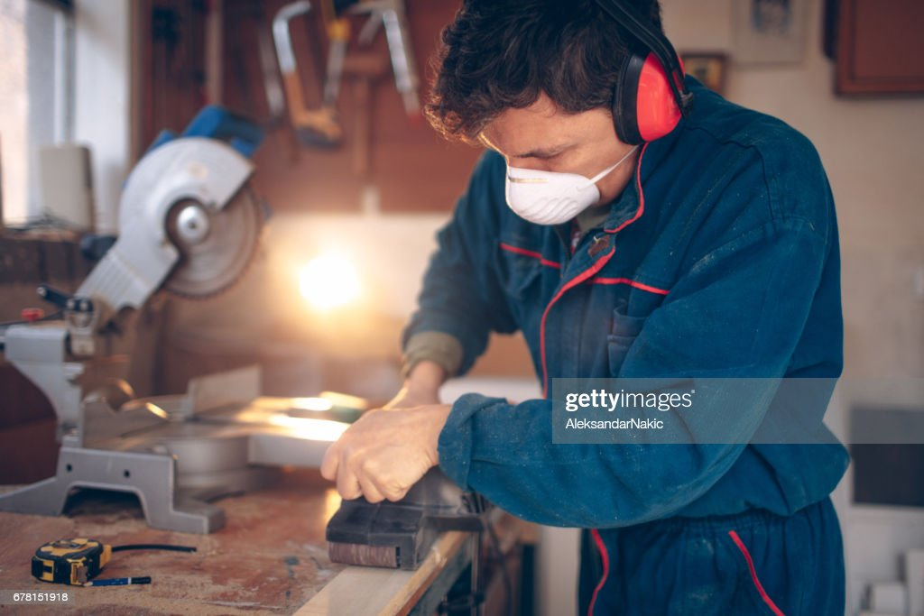 Photo of a carpenter being busy treating wood in his workshop