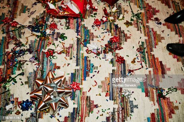 carpet covered with confetti bows and wrapping paper after holiday party - messy house after party stock pictures, royalty-free photos & images