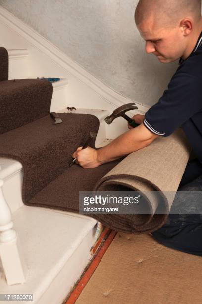 Carpet Fitter using tucking tool on stairs