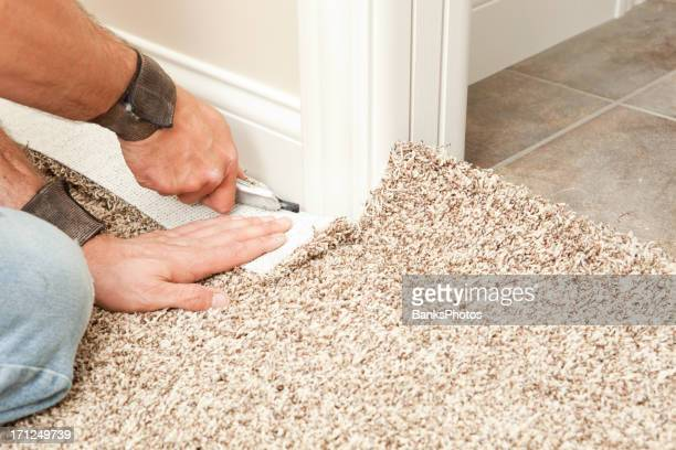 Carpet Installer Using Knife to Trim Wall Edge