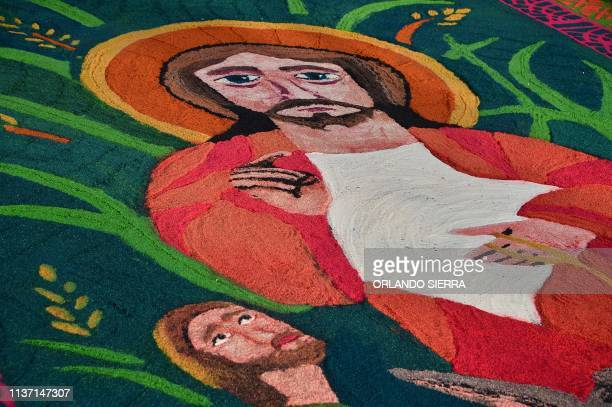 A carpet made out of coloured sawdust depicting religious images is seen in Tegucigalpa during Palm Sunday celebrations on April 14 2019 For...