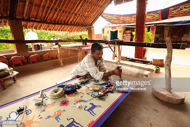 Carpet maker weaving on large floor loom