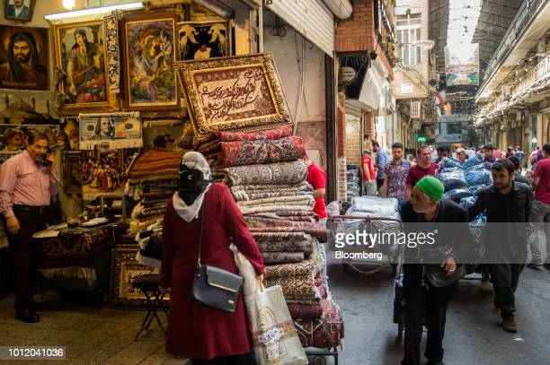 Carpet traders wheel their wares past a store selling Persian rugs and framed pictures inside the Grand Bazaar in Tehran Iran on Monday Aug 6 2018...