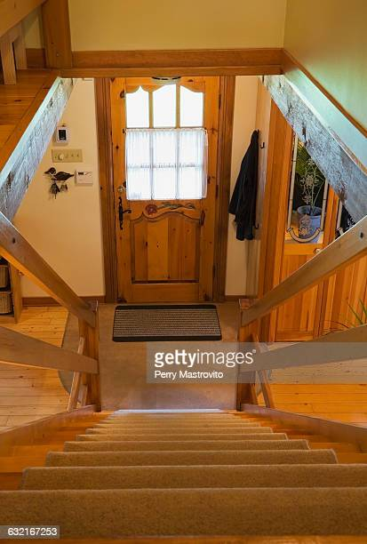 Carpeted wooden stairs and main entrance inside a Canadian cottage style log home